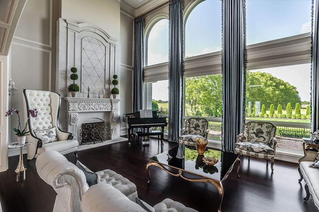 Traditional style living room with 2-story windows and custom fireplace